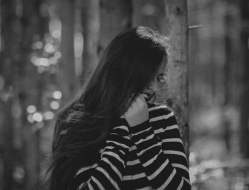 photo black-and-white grayscale photography of woman wearing striped sweater standing tree free for commercial use images
