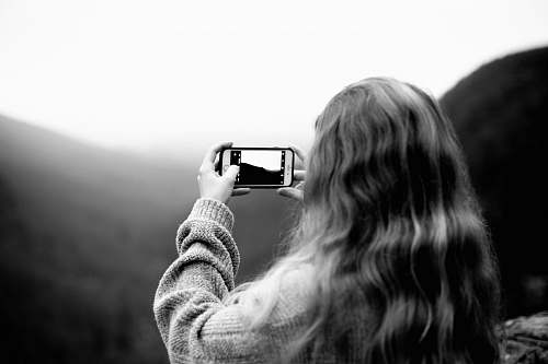 photo person grayscale photography of woman wearing sweater using smartphone taking picture black-and-white free for commercial use images