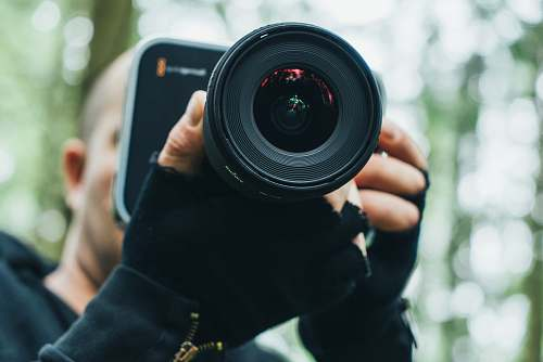 photo person man holding black DSLR camera camera free for commercial use images