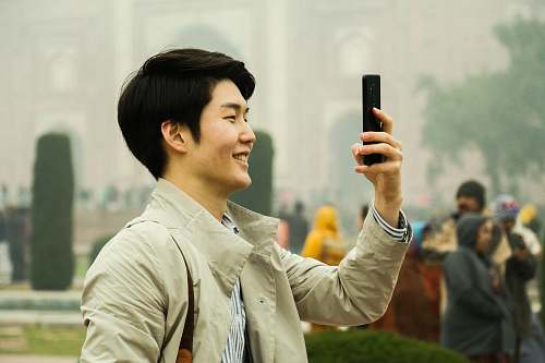 photo person man holding smartphone during daytime face free for commercial use images