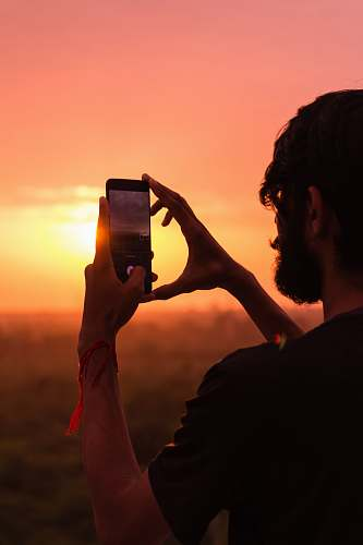 photo person man holding smartphone on high ground during golden hour outdoors free for commercial use images