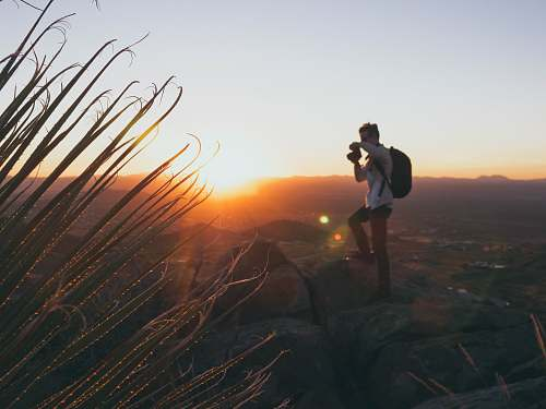 person man standing on cliff during golden hour photographer
