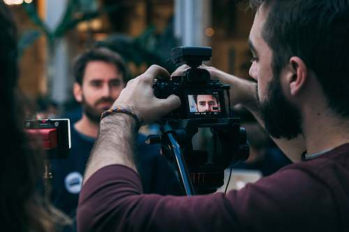 photo person man taking video of standing man wearing black crew-neck top camera free for commercial use images
