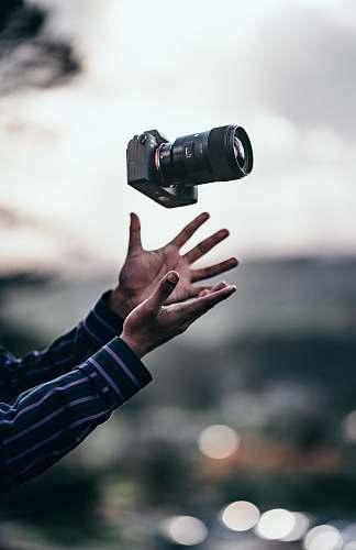 person man wearing blue dress shirt catching black DSLR camera camera