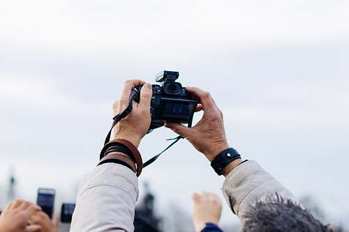 photo person person holding black DSLR camera taking picture during daytime camera free for commercial use images