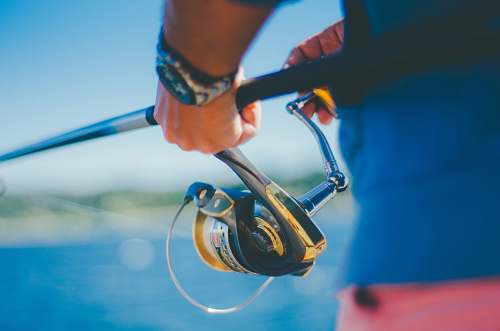person person holding black fishing rod with fishing reel outdoors