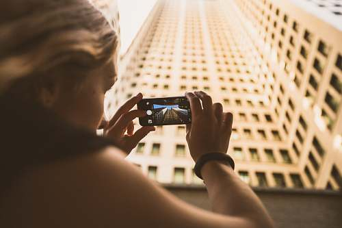 person selective focus photography of woman taking low angle photo of high-rise building people