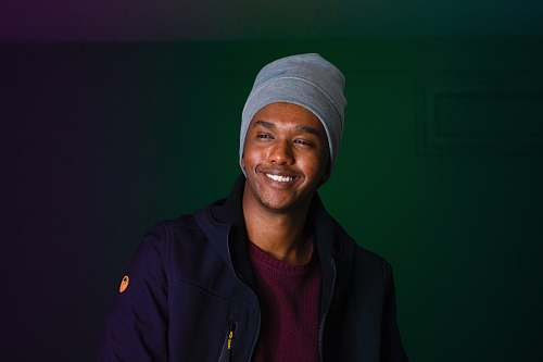 person smiling man wearing knit cap and blue jacket black