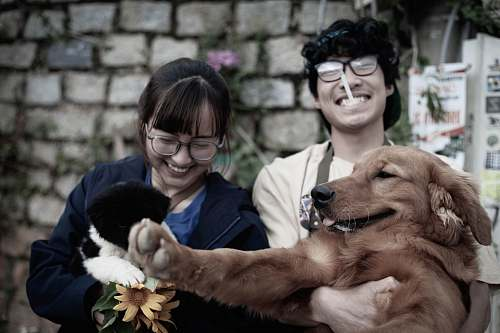 person two smiling woman and man while carrying dog accessories