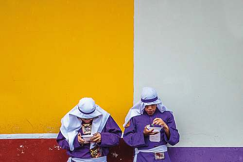 person two standing men wearing purple long-sleeved top leaning on white, yellow, purple, and red painted wall people
