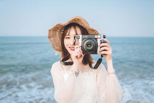 photo person woman holding camera at the beach electronics free for commercial use images