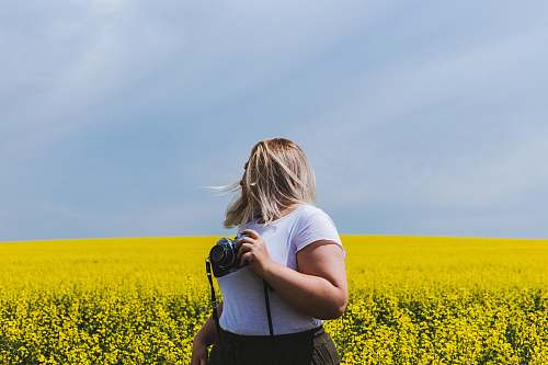 people woman holding DSLR camera standing in front of yellow flower field person