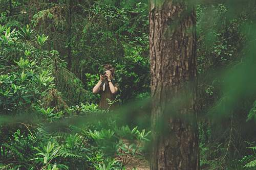 person woman in green dress taking picture in the woods tree