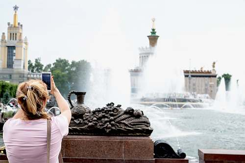 photo person woman taking photo of water fountain water free for commercial use images