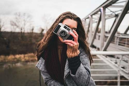 camera woman using camera leaning on handrail near bridge electronics