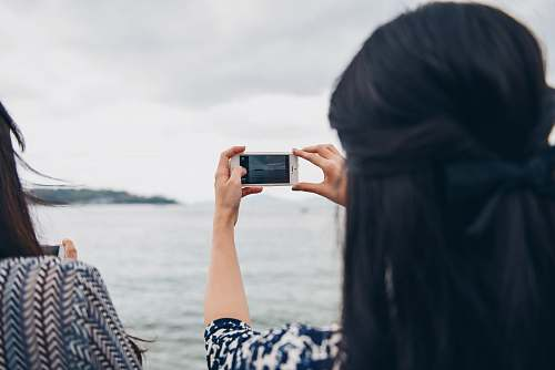 photo person woman using smartphone in front of seawater women free for commercial use images