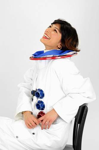 person woman wearing astronaut suit smiling while sitting on chair and looking up people