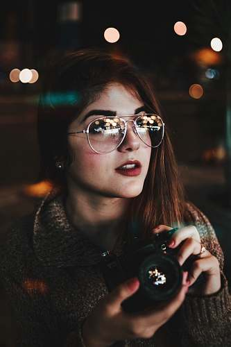 people woman wearing silver-colored Aviator-style sunglasses holding camera bokeh photography person
