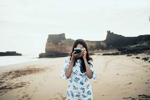 photo person woman wearing white and blue floral dress holding black and gray camera diu free for commercial use images