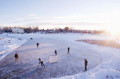 ice skating group of people playing outdoor hockey during winter game
