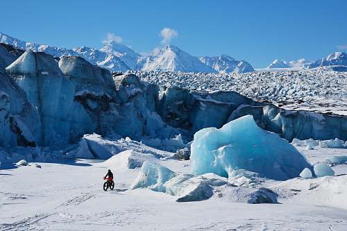 mountain man using bicycle on snow glacier