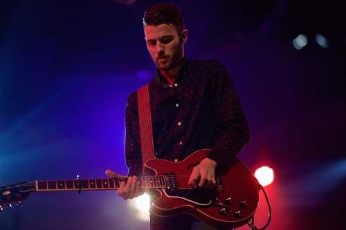 person man playing black electric guitar guitar