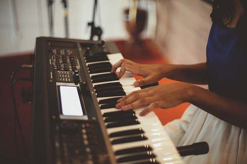 piano person playing a black electronic keyboard keyboard