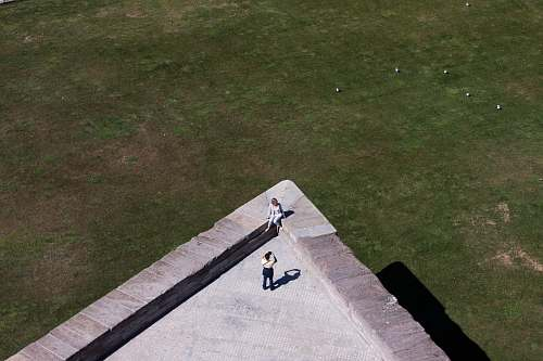 photography aerial photo of two person taking photo on top of building grass