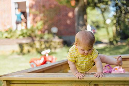 person baby trying to get out of his crib kid