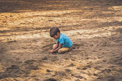 photo sand boy playing on sand during daytime outdoors free for commercial use images