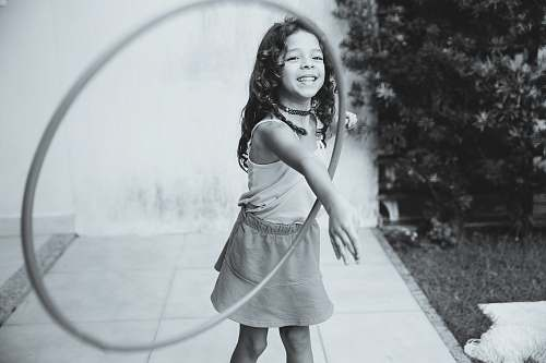 human grayscale photography of girl playing with hula hoop person