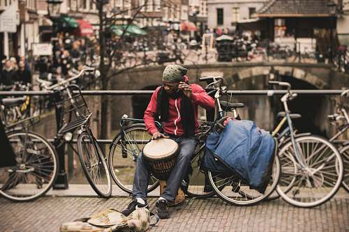 photo person man in red shirt playing darbuka drum while sitting on gray bike near at deck rail bicycle free for commercial use images
