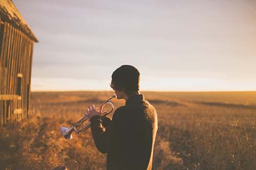 person man playing trumpet outside house on field during daytime music