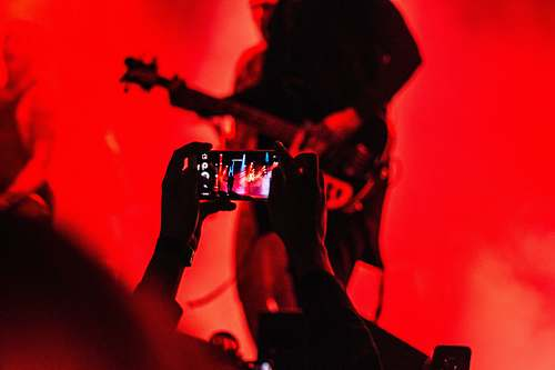 photo music person holding smartphone in front of a person playing guitar on stage phone free for commercial use images