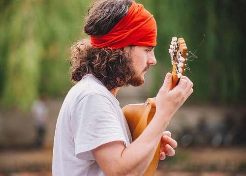 human shallow focus photography of man playing guitar outdoors playing
