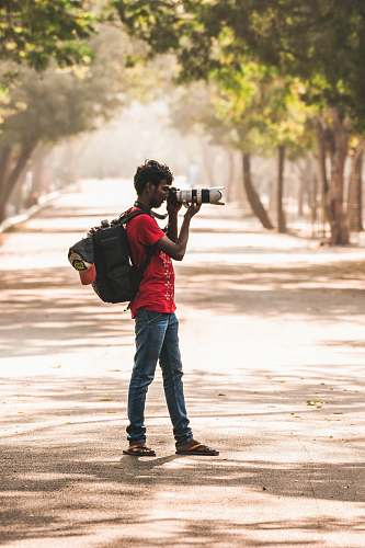photo human man in red t-shirt holding black DSLR camera taking photos while standing on grey asphalt road during daytime apparel free for commercial use images
