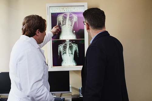 human man in white coat explaining X-Ray results to man in black suit jacket clothing