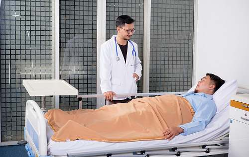 human man lying on bed talking to doctor people