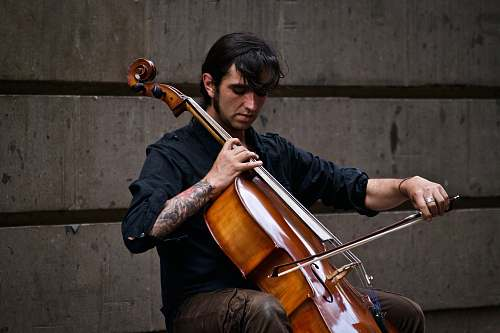 music man playing cello near wall musician