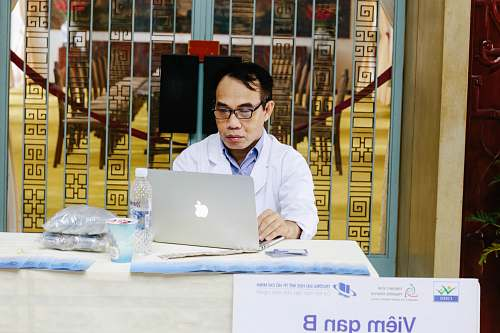 photo human man using silver MacBook near blue metal gate computer free for commercial use images