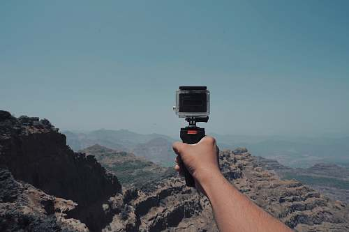 photo human person holding action camera near Grand Canyon photo free for commercial use images