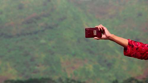 photo human person holding maroon smartphone photo free for commercial use images