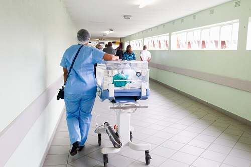 medical person walking on hallway in blue scrub suit near incubator hospital
