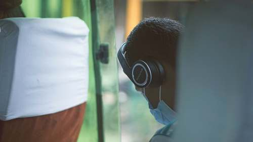 human person wearing black wireless headphones and blue mask doctor