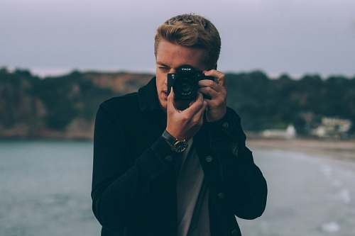 human shallow photography of man holding camera people