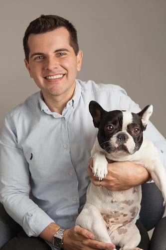 human smiling man holding French bulldog dog