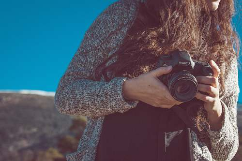 photo human woman holding black Canon DSLR camera canon free for commercial use images