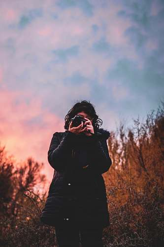 photo human woman in black jacket holding DSLR camera photo free for commercial use images