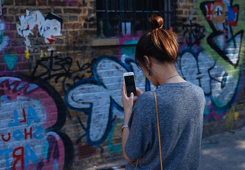 photo people woman looking at smartphone graffiti free for commercial use images