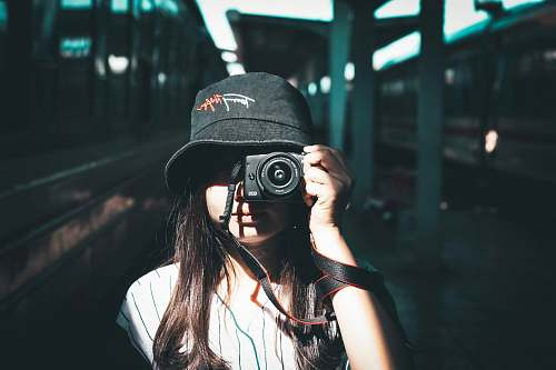 photo human woman wearing black bucket hat holding camera photo free for commercial use images